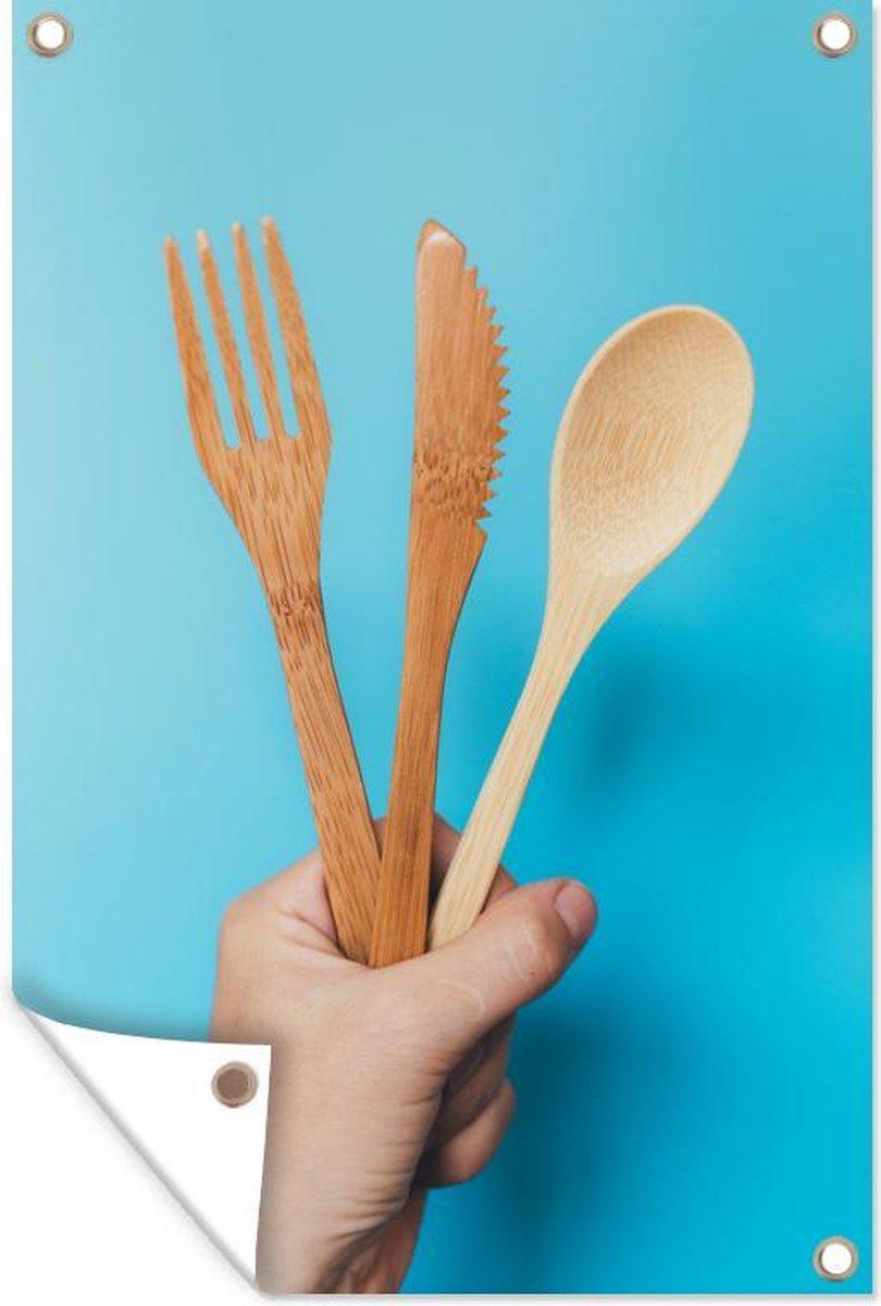 Tuinposter Bestek - Woman hand holding bamboo cutlery set with spoon, fork and knife 120x180 cm - Tuindoek/Buitencanvas/Schilderijen voor buiten (tuin decoratie) XXL / Groot formaat!
